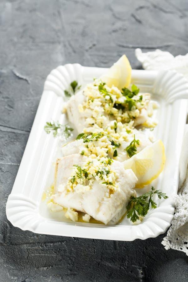 Les poissons blancs ont fait cuire avec de la sauce à persil et à citron photographie stock