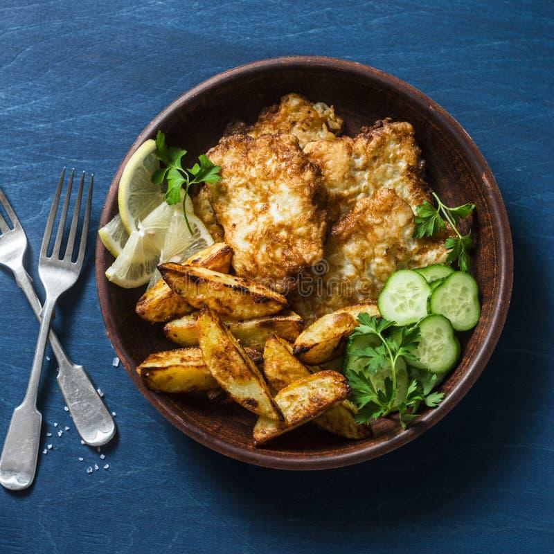 Les poissons et l'ail frits ont fait des pommes de terre cuire au four sur un fond bleu, vue supérieure image stock