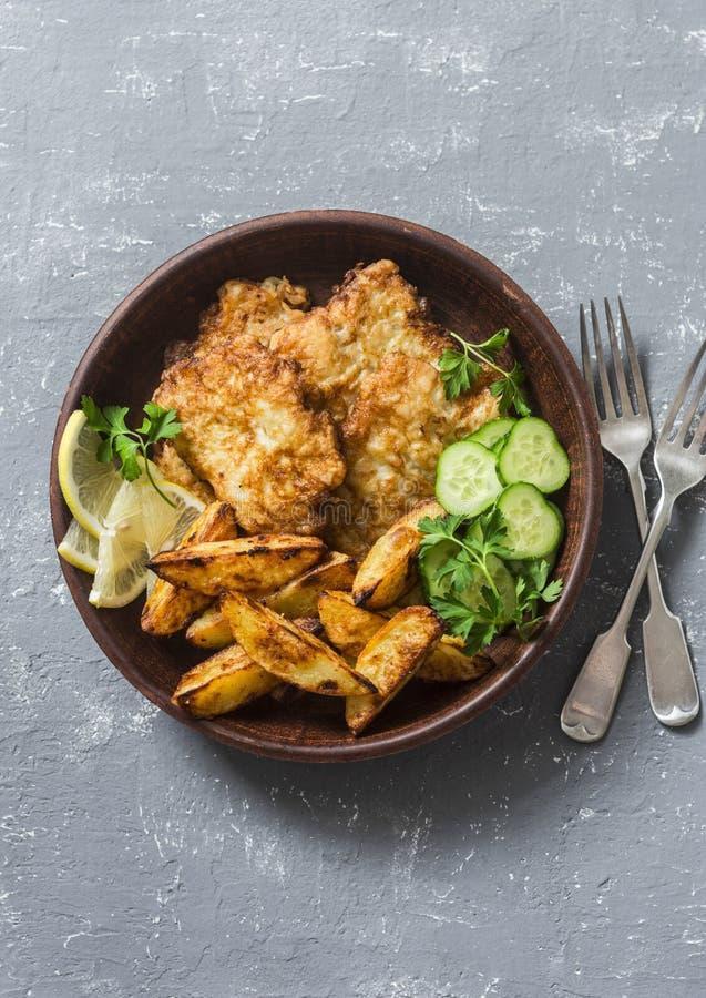 Les poissons et l'ail frits ont fait des pommes de terre cuire au four sur un fond gris, vue supérieure Casse-croûte britannique  photos stock