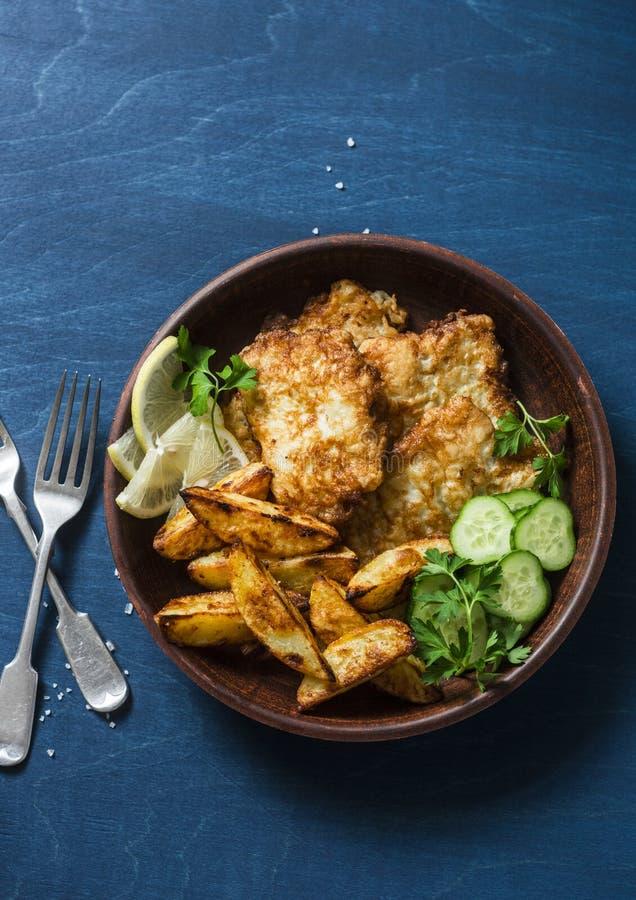 Les poissons frits et l'ail ont fait des pommes de terre cuire au four sur un fond bleu, vue supérieure Casse-croûte britannique  photos stock