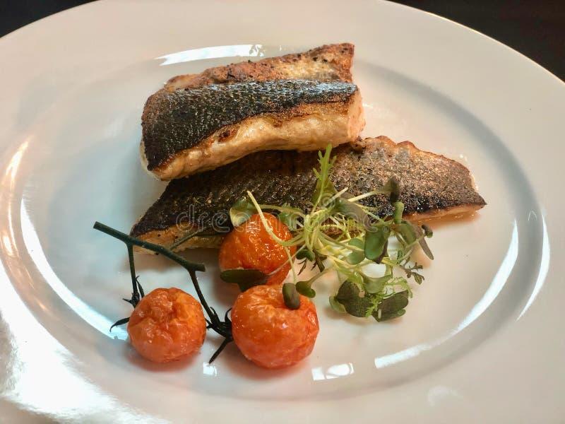 Les poissons frits par casserole de bar de mer ceignent d'un bandeau dans un plat avec le fond noir images stock