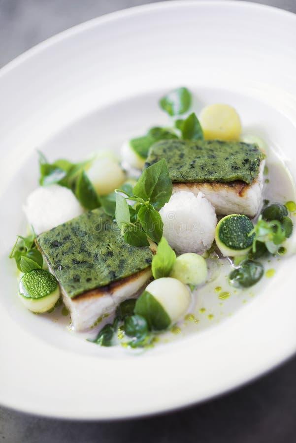 Les poissons grillés avec l'herbe couvrent d'une croûte et ont bouilli des légumes dans le sauc crème photo stock