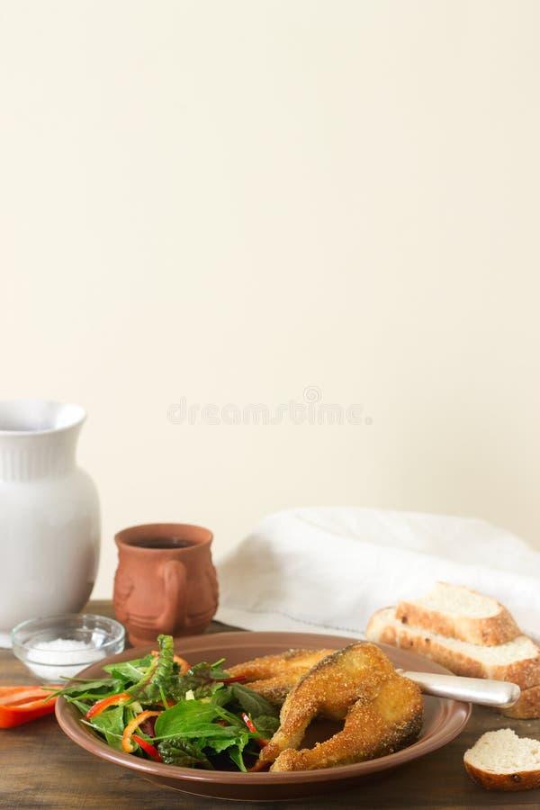 Les poissons ont fait frire en farine de maïs, servie avec de la salade, le pain et le vin photos libres de droits