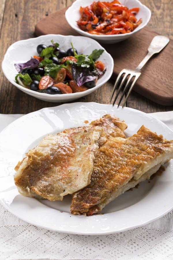 Les poissons roses frits ceignent d'un bandeau d'un plat blanc photos stock