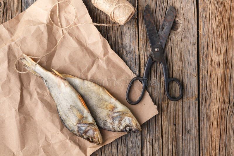 Les poissons salés sèchent sur de vieilles tables en bois images stock