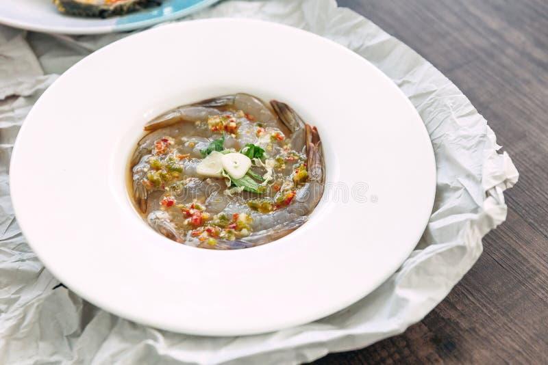 Les poissons Sauce-ont fermenté les crevettes crues avec l'ail frais et le piment a servi dans le plat blanc photo libre de droits
