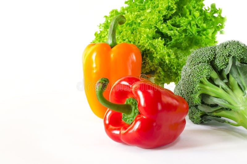 Les poivrons rouges et oranges juteux avec une queue verte se trouve ? c?t? du paquet de laitue et le brocoli sont sur un fond bl photo stock