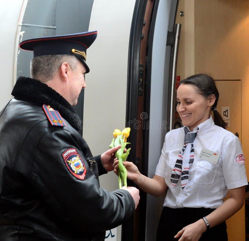 Les policiers donnent des fleurs au women& x27 ; jour de s photos stock