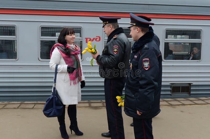 Les policiers donnent des fleurs au women& x27 ; jour de s images libres de droits