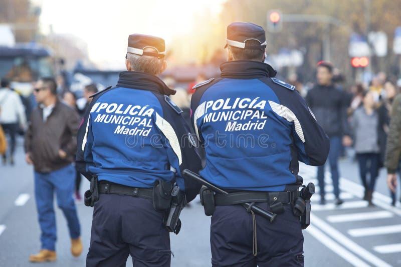 Les policiers patrouillent sur l'avenue et la lumière du soleil de Castellana photographie stock