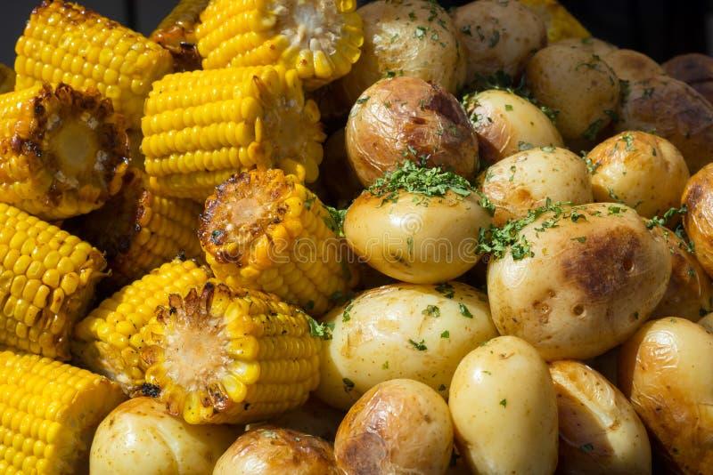 Les pommes de terre dans le persil et le maïs ont fait cuire au four sur le gril photographie stock libre de droits
