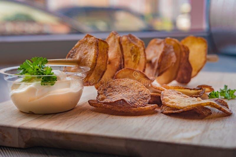 Les pommes de terre ont coupé en tranches, sur un bâton images stock