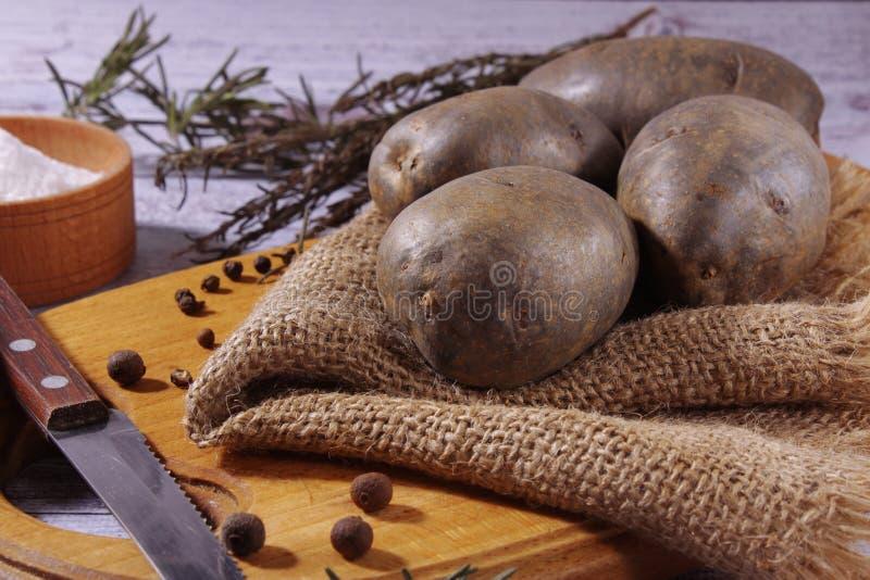 Les pommes de terre organiques et pourpres fraîches se trouvent sur une serviette, sur une planche à découper Cuisson de la nourr photographie stock