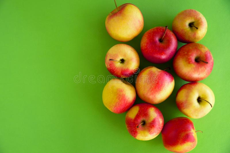 les pommes fraîches juteuses Jaune-rouges se trouvent sur un fond vert fruit frais du jardin R?gime photographie stock libre de droits