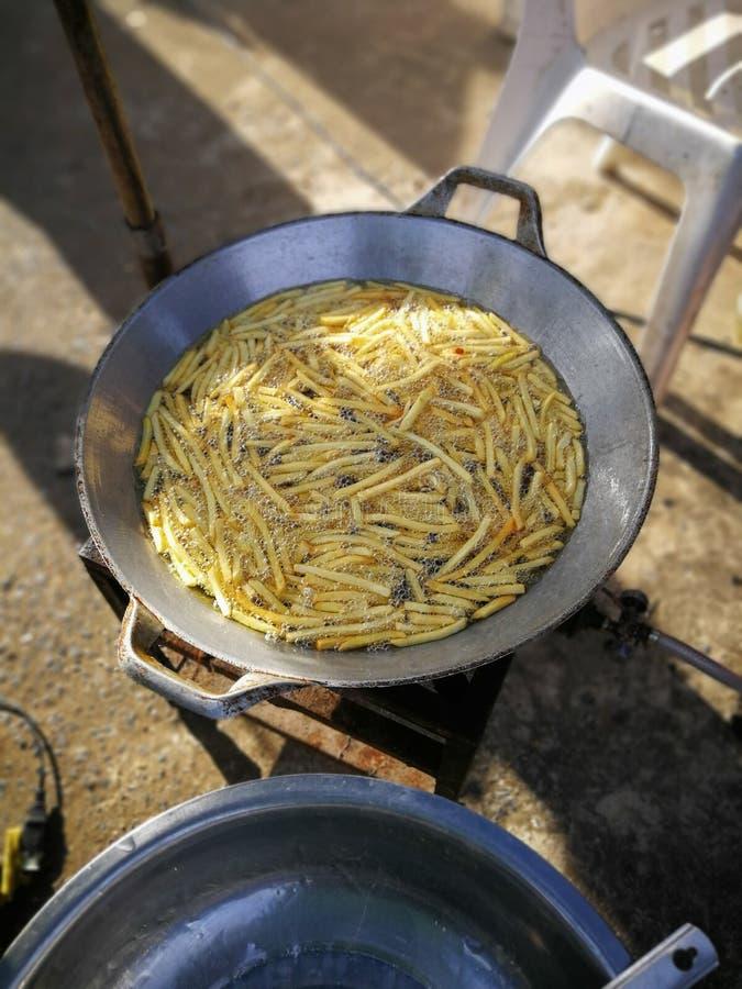 Les pommes frites délicieuses cuisent à la friteuse par avec de l'huile de ébullition dans le pot ou le p photo libre de droits