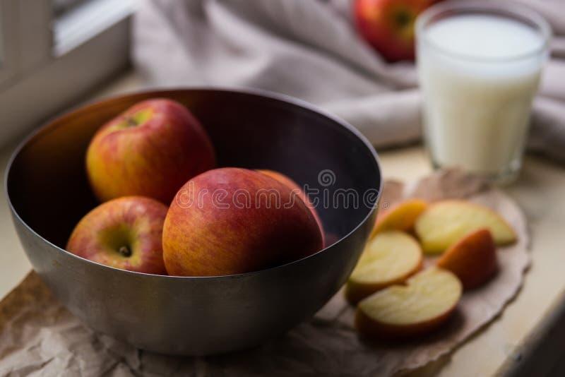 Les pommes rouges fraîches dans un fer élégant bombent le mensonge sur un filon-couche blanc de fenêtre Des tranches d'Apple et u images libres de droits