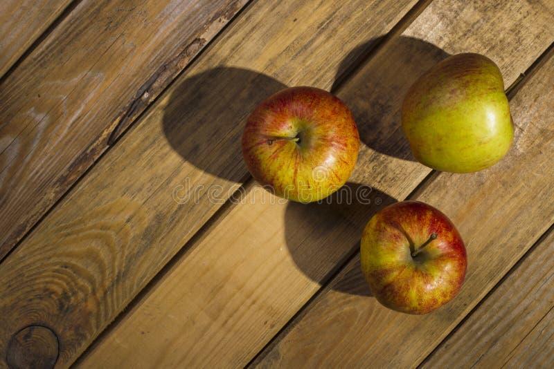 Les pommes se trouvant sur le fond en bois image stock