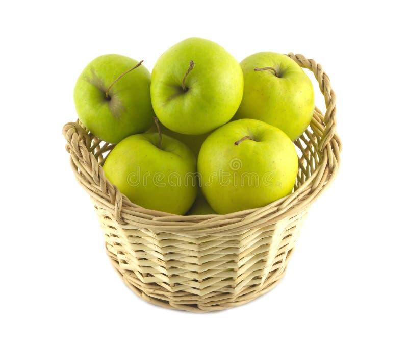Les pommes vertes mûres à l'intérieur du panier en osier brun ont isolé le plan rapproché photo stock