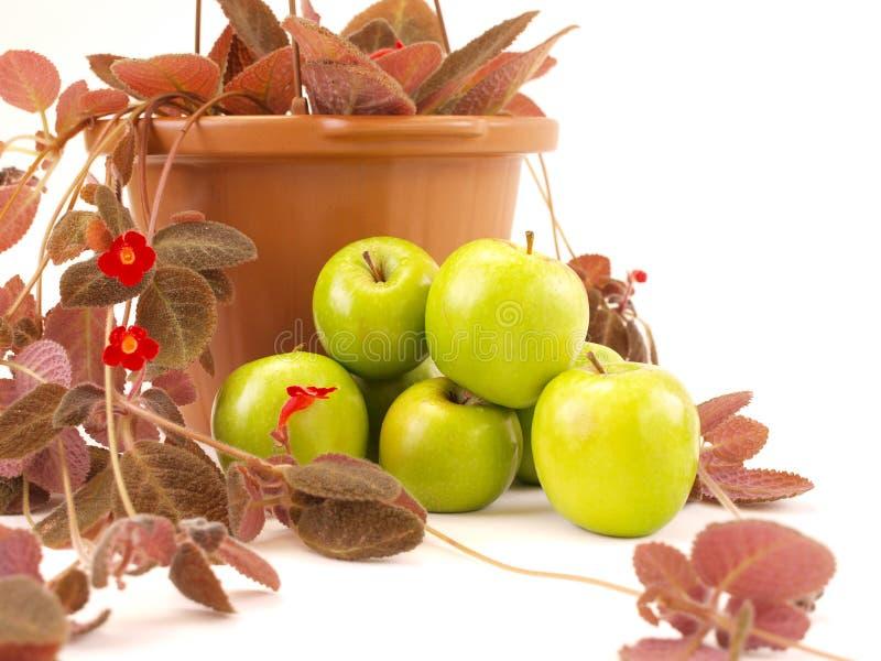 Les Pommes Vertes Ont Empilé Près Des Fleurs Et Du Vase Rouges à Brown Photo stock