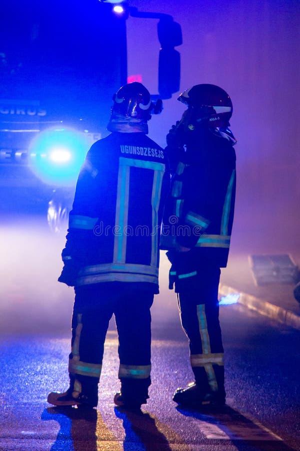 Les pompiers dirigent le courant de l'eau sur la maison brûlante bâtiment dans le plein enfer flamboyant, et un combat de sapeur- image libre de droits