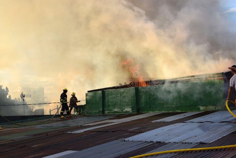 Les pompiers et les volontaires sur le feu mis par dessus de toit utilisant le tuyau d'incendie pendant le feu de maison qui a ét images stock