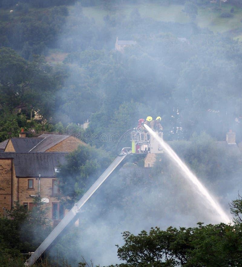 Les pompiers sur une plate-forme élevée éteignant le feu aux anciens walkeys obstrue le moulin hebden dedans le pont photos libres de droits