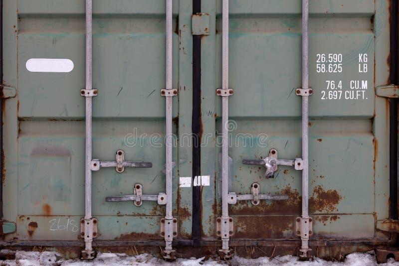 Les portes d'un grand vieux conteneur sont peintes en plan rapproché en vert avec la rouille, avec les serrures en tuyau et le té images libres de droits