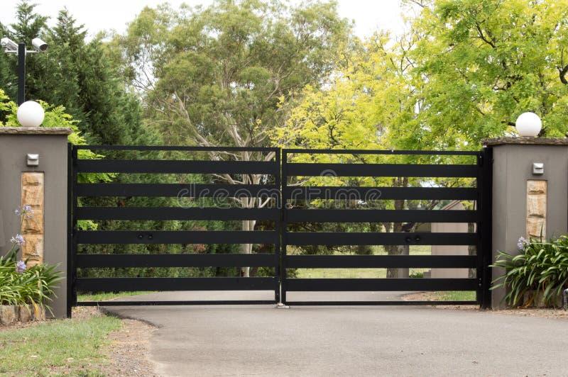 Les portes noires d'entrée d'allée en métal ont placé dans la barrière photos stock