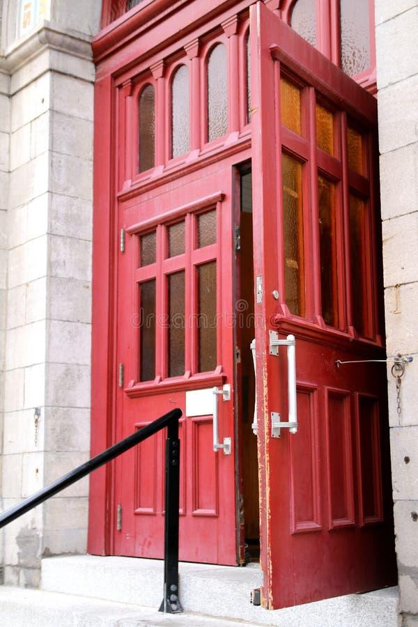 Les portes rouges sont l'entrée à cet immeuble de bureaux photo libre de droits