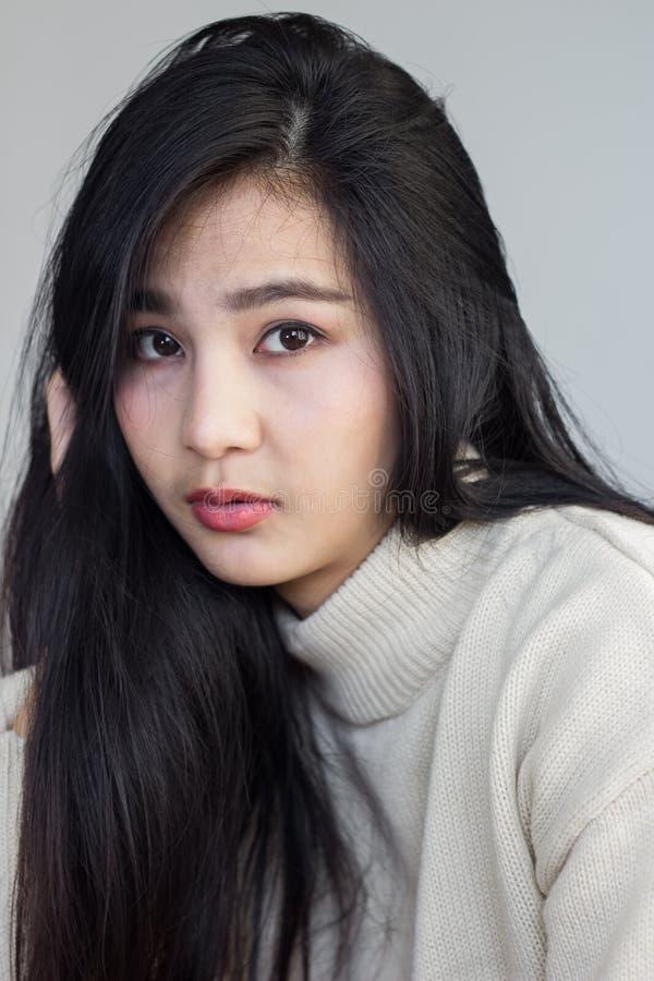 Les poses asiatiques de fille manipulent sa tête photographie stock