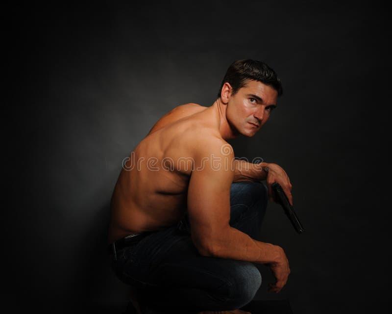 Les poses sexy d'homme pour l'appareil-photo image stock