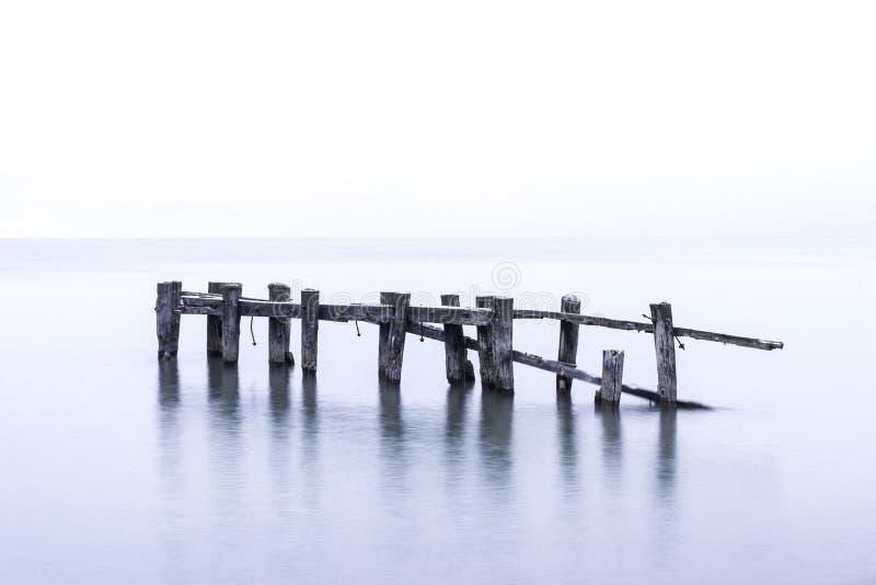 Les poteaux en bois cassés rustiques de pilier se tenant dans le lac bleu calme arrosent photos stock