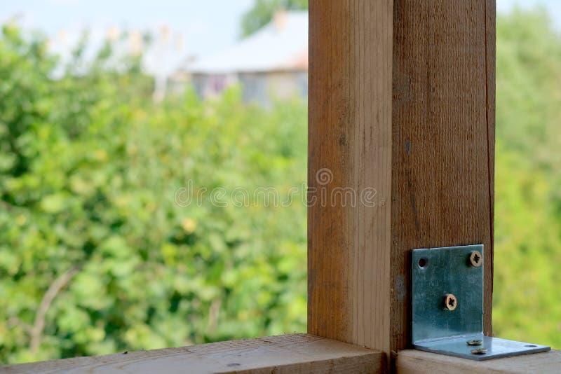 Les poteaux en bois fixes par le coin en métal avec des vis au-dessus de nature verte ont brouillé le fond photo stock