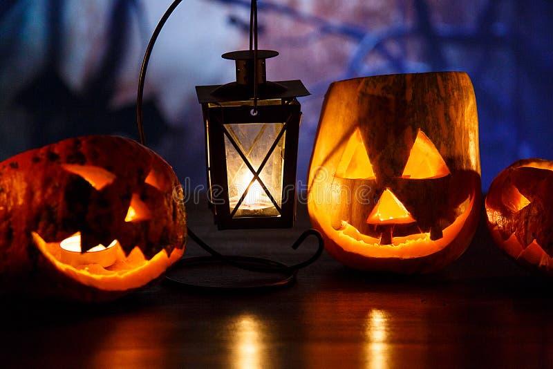 Les potirons oranges avec les visages, la lanterne et les bougies effrayants se trouve sur la table devant le fond bleu-foncé C?l photographie stock