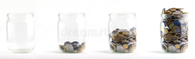 Les pots en verre avec des pièces de monnaie aiment le diagramme, d'isolement - concept de l'épargne image stock