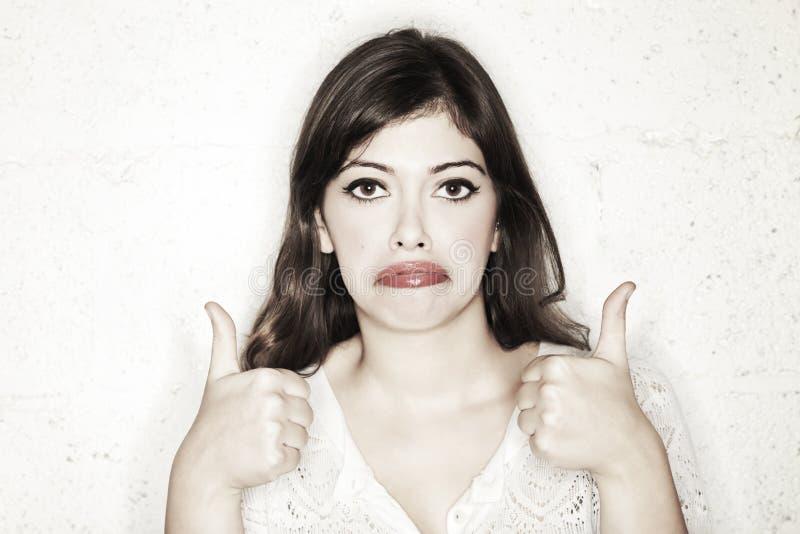 Les pouces sarcastiques lèvent la femme triste photo stock