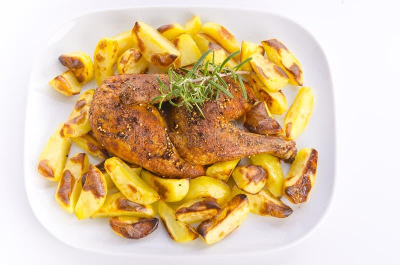 Les poulets rôtissent avec des pommes de terre de traitement au four photographie stock libre de droits