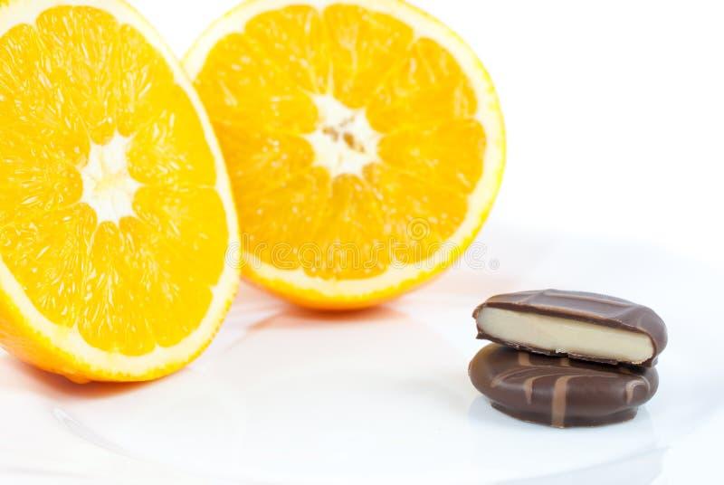 Les pralines avec de la crème orange ont enduit en chocolat foncé lisse de plat image stock