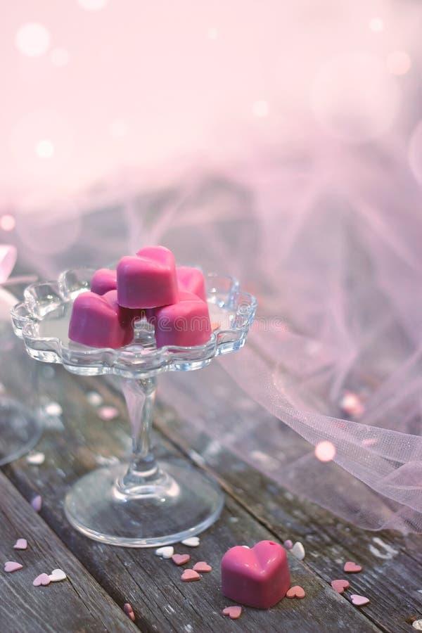 Les pralines roses de chocolat au coeur forment, dans la belle cloche en verre, images stock