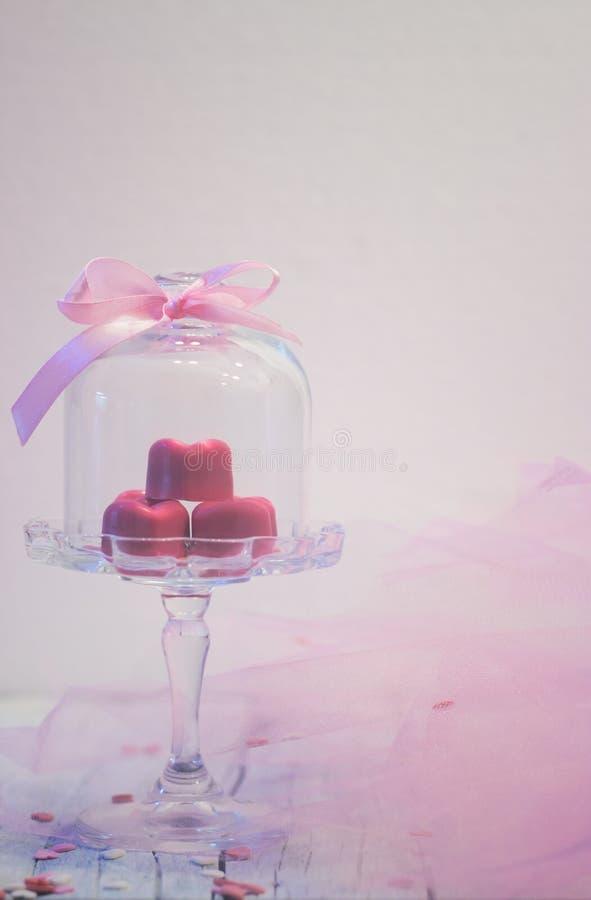 Les pralines roses de chocolat au coeur forment, dans la belle cloche en verre, photographie stock