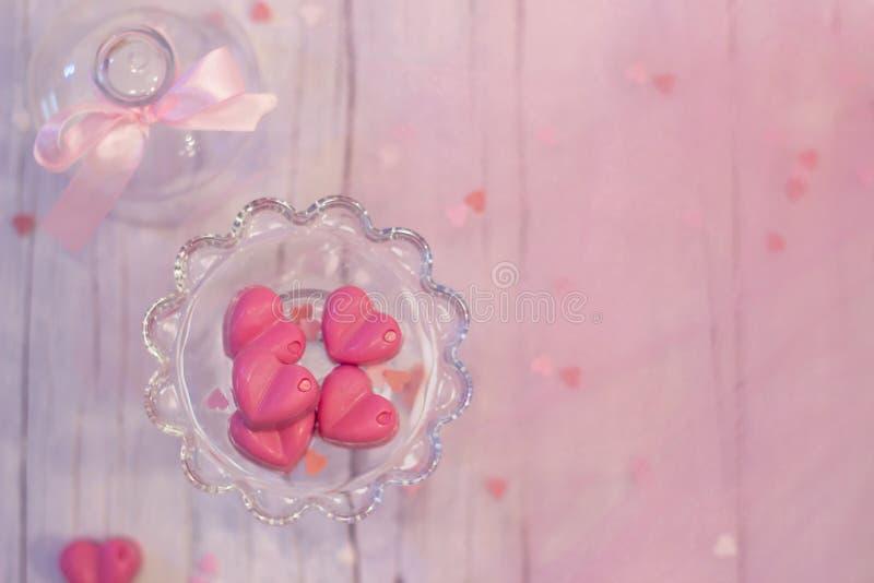 Les pralines roses de chocolat au coeur forment sur le fond en bois blanc avec l'espace rose de copie images stock