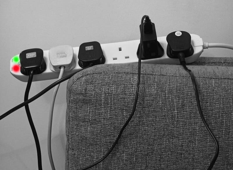 les prises dangereuses de surtension de surcharge de danger branchent le danger électrique de maison de prise images stock