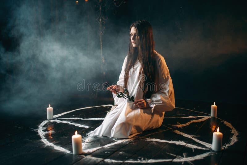 Les prises de femme brûlées ont monté dans des mains, rituel magique foncé photo libre de droits
