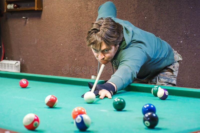Les prises de joueur visent la boule dans les billards photos stock