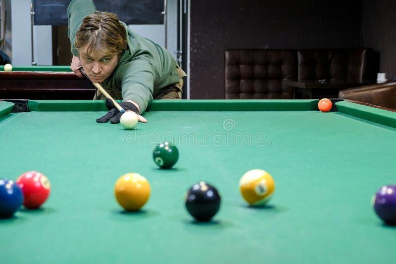 Les prises de joueur visent la boule dans les billards photographie stock