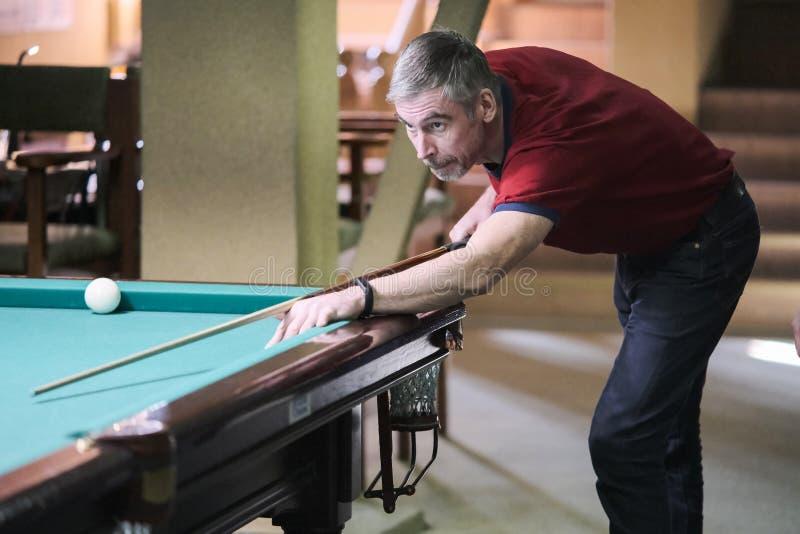 Les prises de joueur visent la boule dans les billards image libre de droits