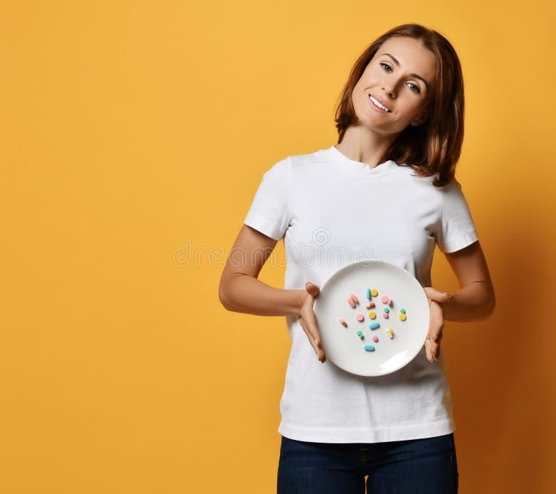 Les prises de sourire heureuses de femme démontre un plat avec différentes drogues de perte de poids de prescription de supplémen photo libre de droits