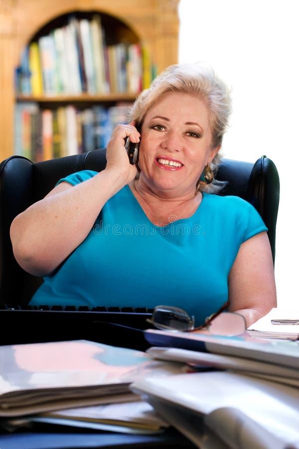 Les prises Relaxed de femme appellent au bureau image stock
