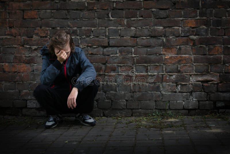 Les problèmes des adolescents, enfant triste s'asseyant dans une chambre noire pense photo stock