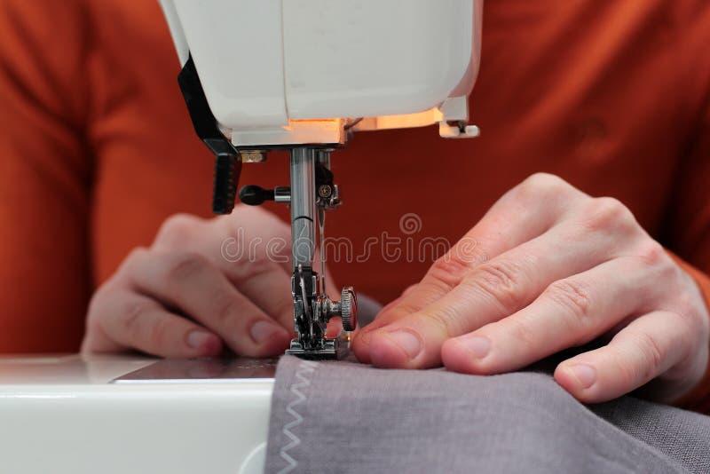 Les processus de coudre le lin sur la machine à coudre cousent la machine à coudre Linum des mains des femmes machine à coudre et photo libre de droits